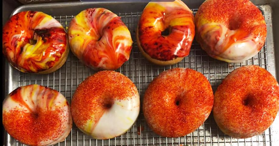 multicolor red and orange vanilla icing doughnuts with sprinkles